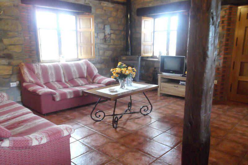 Salón con chimenea de leña de Casa Juntana