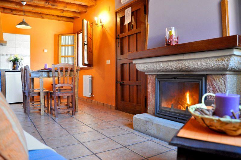 Amplio salon con chimenea de leña en los Apartamentos Rurales Los LLares